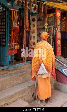 Hindu sadhu (holy man) outside shop selling beads and other handicrafts in market near Durbar Square, Patan, Kathmandu Valley, Nepal - Stock Photo