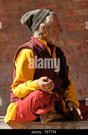Hindu sadhu (holy man) meditating in Durbar Square, Kathmandu, Nepal - Stock Photo