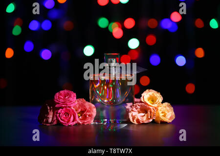 Transparent bottle of perfume with beautiful flowers on dark table against blurred lights - Stock Photo