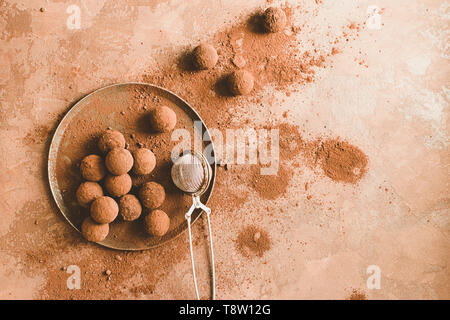 Handmade chocolate truffle on a plate. Dark chocolate candies in cocoa powder on a dark brown background. Flat layout. - Stock Photo