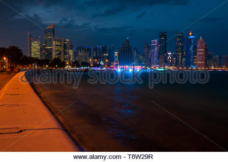 The skyscrapers of the new West Bay area of Doha city seen from Al Corniche in the evening. - Stock Photo