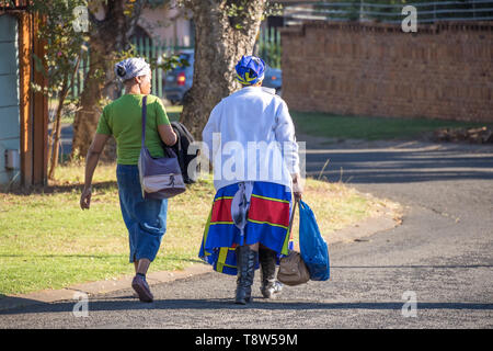 Johannesburg, South Africa - unidentified black women walk home in the afternoon from their jobs as domestic workers in the city - Stock Photo