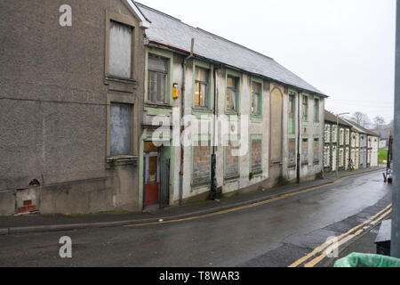 Boarded up decaying row of buildings / shops in Wales, UK - Stock Photo