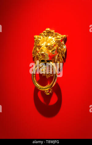 Knoker in the form of a golden lion on the background of the red surface of the door. - Stock Photo