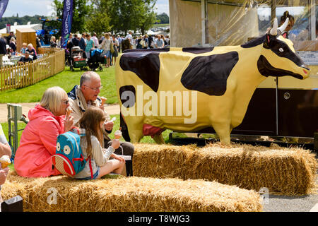 People (man woman child) eating ice creams by mobile catering van & large life-size model of a cow - Great Yorkshire Show, Harrogate, England, UK. - Stock Photo