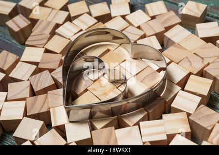 Iron heart symbol leaning on a structure made of many other blocks with several of them still lying scattered on a textured rustic wooden desk. - Stock Photo