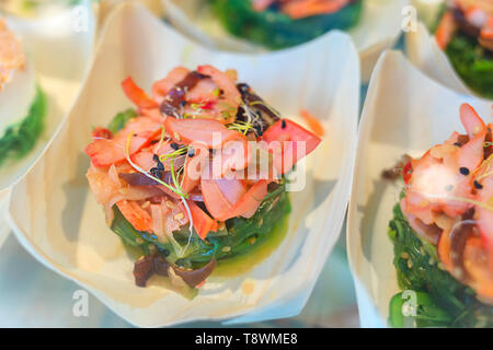 Traditional spanish tapas with fresh seafood served in small cup – delicious squid with marinated seaweed salad and germinated alfalfa sprouts - Stock Photo