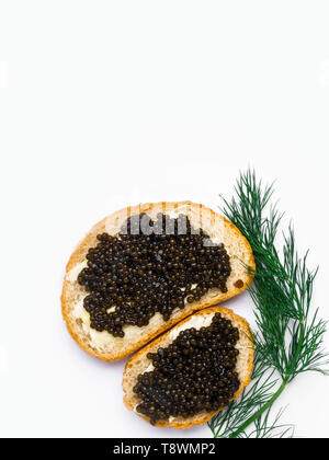 Two slices of baguette with butter, dill and black caviar isolated on white background. Luxurious delicacy appetizer. Copy space - Stock Photo