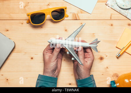 Summertime holiday vacation travel concept with model of airplane on the table, planning new adventure for this summer season, flat lay top view - Stock Photo