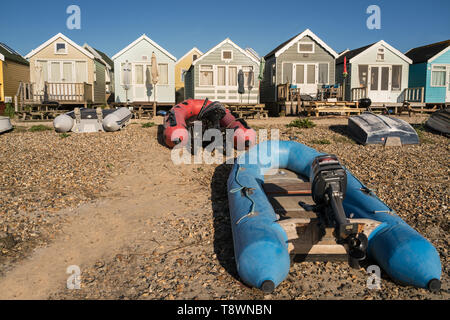 Colourful beach huts and boats in the early evening at Mudeford Sandspit Hengistbury Head near Bournemouth in Dorset - Stock Photo