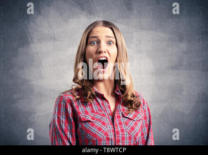 Scared young woman screaming with panic - Stock Photo