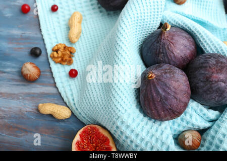 Fresh ripe figs with napkin on color wooden table - Stock Photo