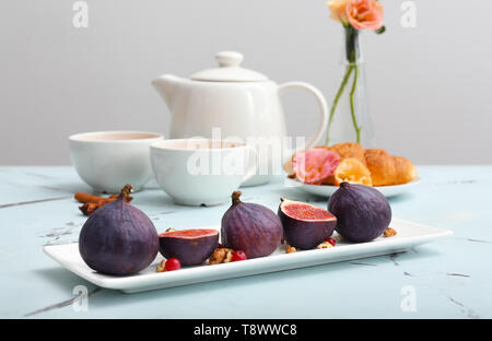 Plate with fresh ripe figs on light table - Stock Photo