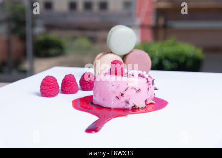 elegant berry tart, colorful macaroons and fresh berries. Blurred background - Stock Photo