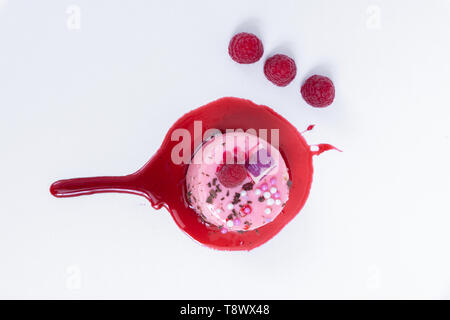 Top up view of the pink cake. With wild berries and chocolate shavings - Stock Photo