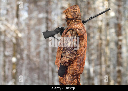 hunter in autumn camouflage with a gun on his shoulder in the winter forest - Stock Photo