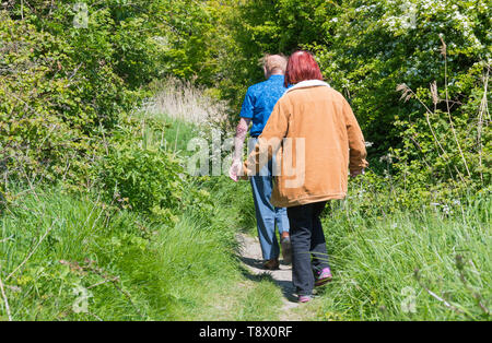 Senior couple of people walking along a country footpath in Spring in West Sussex, England, UK. - Stock Photo