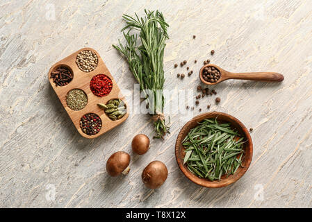 Fresh aromatic rosemary with mushrooms and different spices on light background - Stock Photo