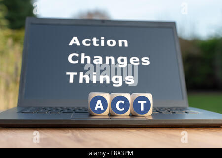 Dice form the abbreviation 'ACT'. Dice placed on a Notebook. The text 'Action changes things' is written on the display. - Stock Photo