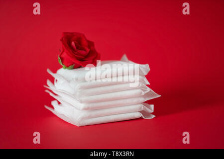 Stack of menstrual pads with red rose on color background - Stock Photo