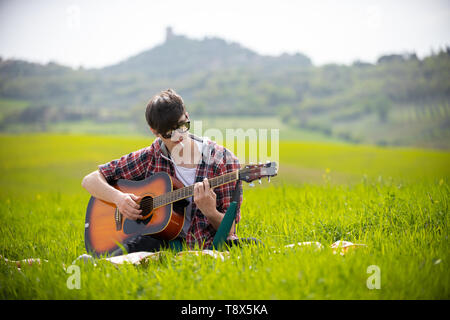 A young man sitting on a bright green meadow playing guitar and smoking cigarette - Stock Photo