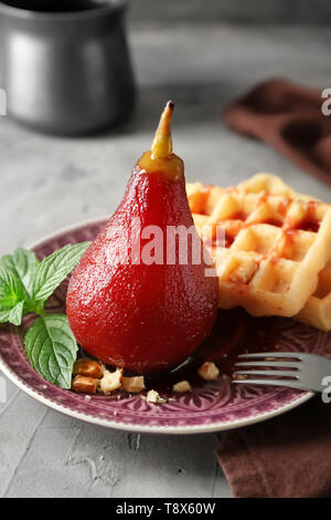 Delicious poached pear in red wine with waffles on plate - Stock Photo
