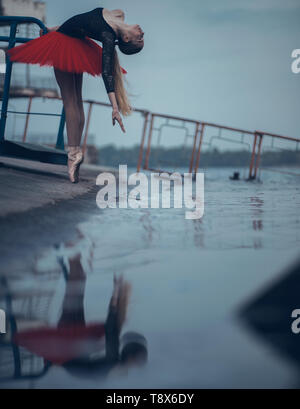 Ballerina dancing on the coast of river in a black and red tutu and her reflection in the water. - Stock Photo