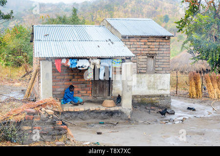 young woman sits on the verandah of her brick house in a village of East Mozambique - Stock Photo