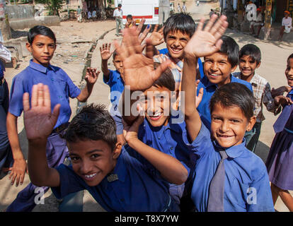 Indian school children laughing and waving in an Indian village, Rajasthan, India - Stock Photo