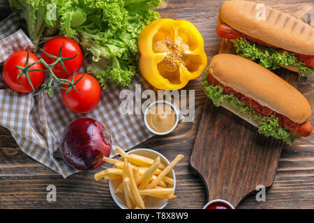 Composition with vegetables and tasty hot dogs on wooden table - Stock Photo