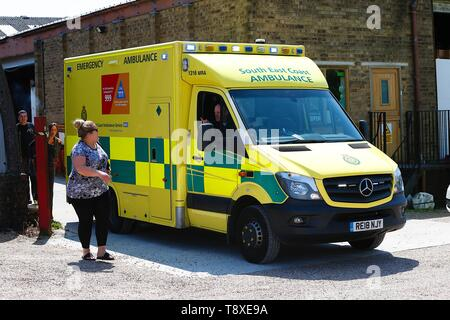 Tenterden, Kent, UK. 15th May, 2019. A Kent Surrey Sussex air ambulance as been dispatched to an incident in the town centre. Medical staff are at scene. The emergency has taken place at the Old Dairy Brewery in the town centre. The driver of a South East Coast ambulance talks to a relative at the scene of the accident. Credit: Paul Lawrenson 2019, Photo Credit: Paul Lawrenson/Alamy Live News - Stock Photo