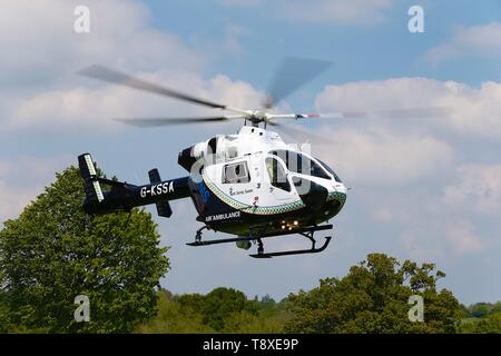 Tenterden, Kent, UK. 15th May, 2019. A Kent Surrey Sussex air ambulance has been dispatched to an incident in the town centre. Medical staff are at scene. The emergency has taken place at the Old Dairy Brewery just off the high street in the town centre. The MD902 Explorer helicopter takes off into the air. Credit: Paul Lawrenson 2019, Photo Credit: Paul Lawrenson/Alamy Live News - Stock Photo