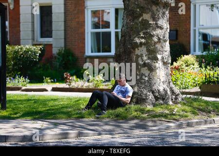 Tenterden, Kent, UK. 15th May, 2019. UK Weather: Beautiful sunny day in Tenterden high street as people walking around the town centre enjoy the lovely hot weather. A young man sits in the shade under a tree. Credit: Paul Lawrenson/Alamy Live News - Stock Photo