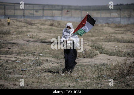 Gaza City, Palestinian Territories. 15th May, 2019. A Palestinian protester holds the Palestinian national flag during a rally to mark the 71st anniversary of Nakba Day, commemorating the mass displacement of more than 700,000 Palestinians who fled or were expelled from their homes in the 1948 War surrounding Israel's creation. Credit: Mohammed Talatene/dpa/Alamy Live News - Stock Photo