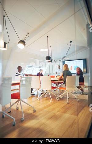 Manager giving a monitor presentation to a diverse group of coworkers sitting around a table inside of a glass office - Stock Photo