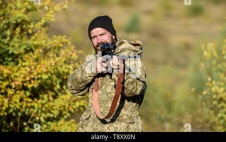 Bearded hunter spend leisure hunting. Focus and concentration of experienced hunter. Hunting masculine hobby concept. Man brutal gamekeeper nature background. Regulation of hunting. Hunter hold rifle. - Stock Photo