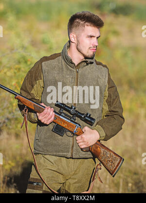 Hunting and trapping seasons. Bearded serious hunter spend leisure hunting. Man brutal unshaved gamekeeper nature background. Hunting permit. Hunter hold rifle. Hunting is brutal masculine hobby. - Stock Photo