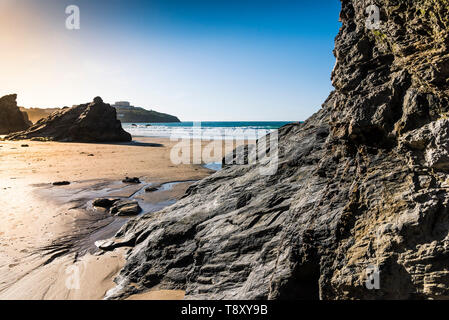 Evening light over rocks exposed at low tide on Great Western Beach in Newquay in Cornwall. - Stock Photo