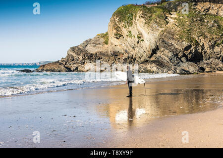 A surfer carrying his surfboard and standing on the shoreline on Great Western Beach in Newquay in Cornwall. - Stock Photo
