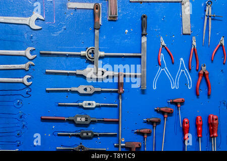 Working tools on blue painted wooden board in a factory storage room. - Stock Photo