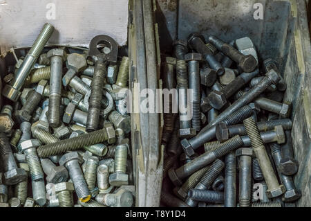 Metal screws and steel bolts in a storage room of a factory. - Stock Photo