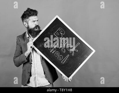 Teaching stressful occupation. Take it easy. Teacher with tousled hair stressful about school year beginning. Teacher bearded man holds blackboard with inscription back to school red background. - Stock Photo
