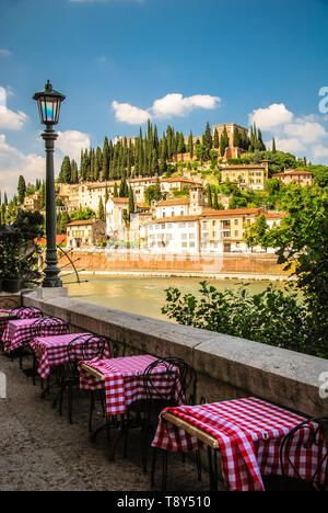 Dining Tables setup along the Adige River in Verona, Italy complete with typical Italian red and white checked tablecloths. - Stock Photo