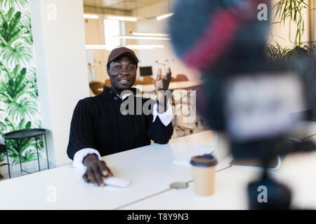 Young african man speaker talking on digital camera recording vlog. African male vlogger or business trainer speaking shooting blog filming reportage  - Stock Photo
