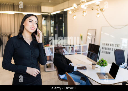 Young office woman talking to someone on her mobile phone while looking into the distance. - Stock Photo