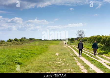 People walking along the coastal pathway leading to Handfast Point on the Jurassic Coast, Dorset, UK - Stock Photo