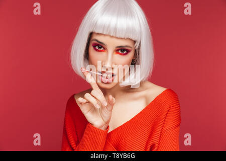 Beautiful young woman wearing bright makeup and white wig standing isolated over pink background, chewing bubblegum - Stock Photo