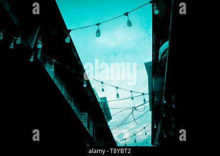 Decorative beautiful  outdoor Party concept idea  string lights bulb blue tine hanging on electricity post in street at night time nobody no people - Stock Photo