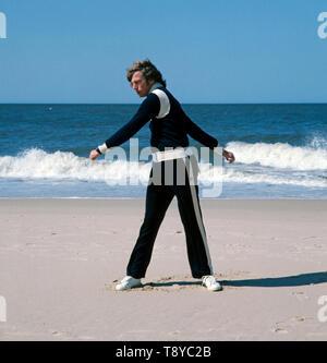 Der deutsche Rennfahrer und Prinz von Bayern Leopold besucht einen Strand, gekleidet in einem Fila Trainingsanzug, ca. in den 1980er Jahren.The German racing driver and Prince of Bavaria Leopold visits a beach, dressed in a Fila tracksuit, circa in the 1980s. - Stock Photo