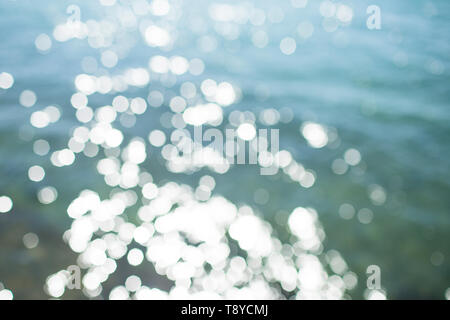 Blue bokeh on abstract background. Blur sea water on sunny day. Water with blurred effect. Summer vacation and wanderlust - Stock Photo